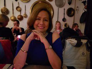 Rosario Marín sentada en una mesa sonriendo, recargada en ambas manos con un vestido azul en un restaurante.