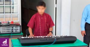 Nino frente a un teclado sobre una mesa, tocándolo.