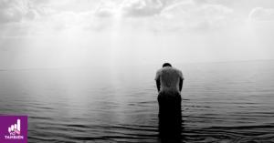 Persona cabizbaja en medio de un océano.