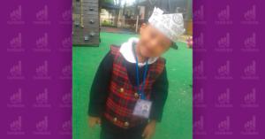 Niño en un patio de escuela, usando uniforme y sonriendo.