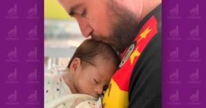 Sopitas abrazando sobre su pecho a su hijo bebé dándole un beso en su cabeza.