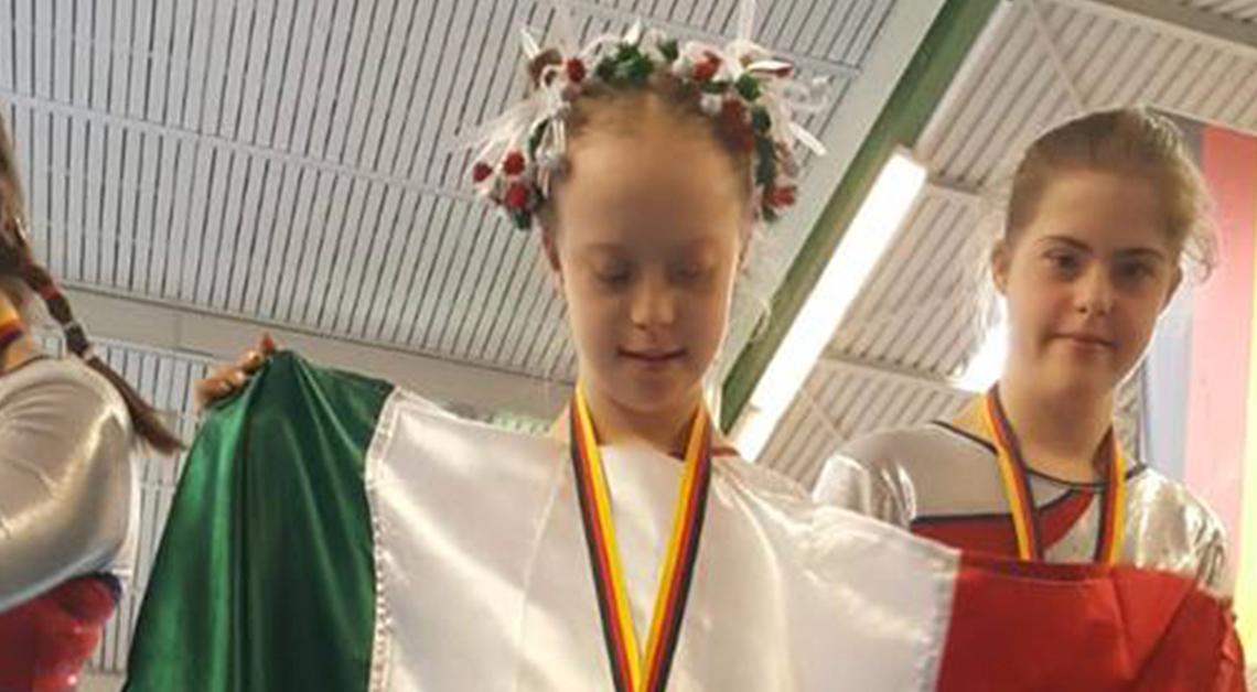 María Bárbara Wetzel aguilar coronada como campeona sosteniendo la bandera de México sobre su pecho, mirándola.