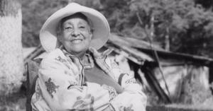 Foto en blanco y negro. Anita de brazos cruzados sonriendo sentada con un sombrero puesto.