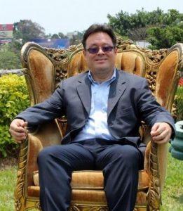 Carlos Saro sentado en un sillón estilo victoriano sonriendo a la cámara.