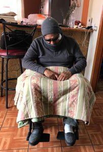 El alcalde disfrazado. Sentado encorvado en una silla de ruedas con suéter, gorro, lentes de sol y una manta sobre su regazo.