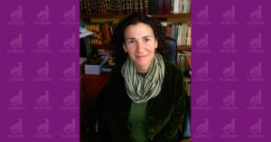 Fotografía de Diana Shinbaum sentada frente a su escritorio, podemos notar un librero detrás de ella mientras ella ve directamente a la camara y sonríe
