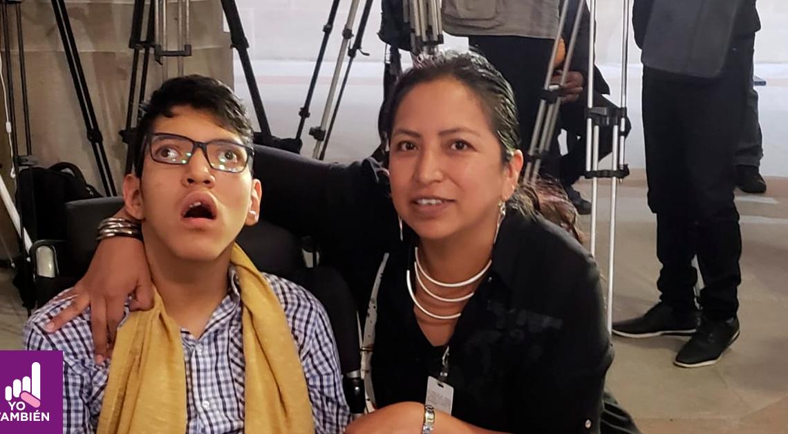 Fotografía de Margarita Garfias abrazando a su hijo Carlos, el está usando una camisa de cuadros morada y ella un sueter color negro. Ambos están sonriendo y viendo a la cámara.