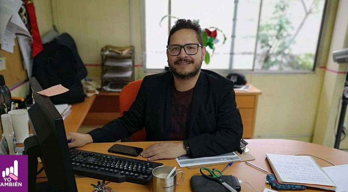 Fotografía de Ernesto Escobedo en su oficina viendo a la camara mientras nos sonríe viste un saco negro y una camisa morada con unos lentes cuadrados negros