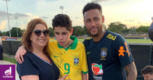 Foto de Nicolas con su playera firmada por los jugadores de la seleccion de brazil con su mama y el jugador Neymar afuera del campo de entrenamiento de la seleccion brasileña
