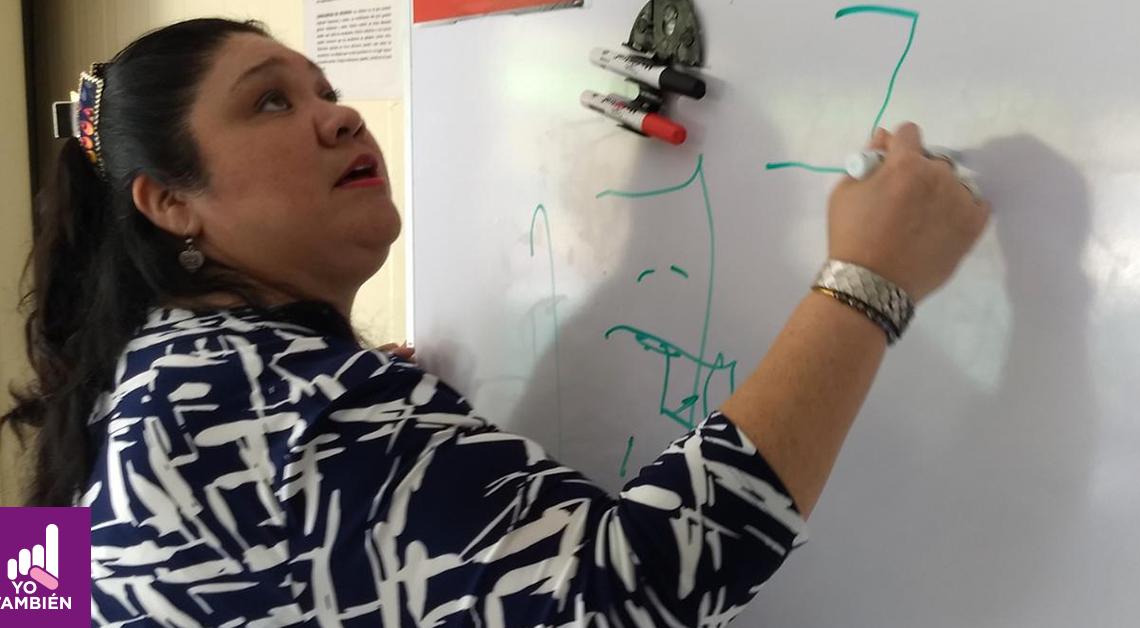 Fotografia de Hilda con una blusa de color negro con lineas blancas con su brazo extendido mientras dibuja en un pizarrón mientras da clases