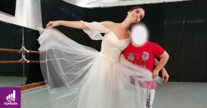 Fotografía de una bailarina con un vestido largo blanco sonriendo abrazando a una niña con pcd