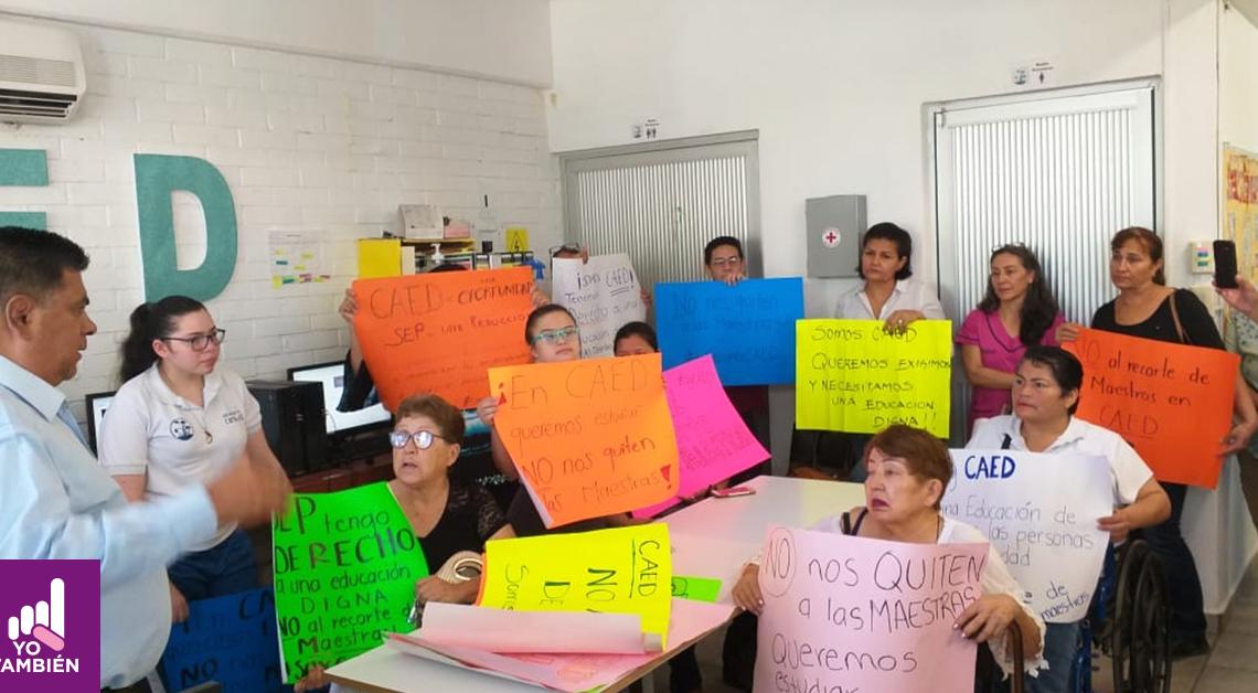 Fotografía de los padres de los niños que atienden a los CAED con pancartas