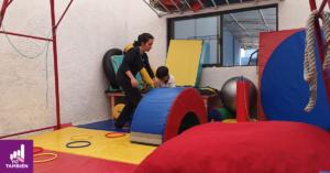 Fotografía de cuerpo completo de una de las cuidadoras de Autismax vestida de negro acompañando a un niño en un cuarto de juegos mientras el sube un pequeño puente