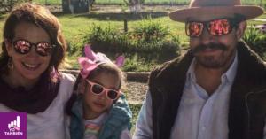 Fotografía de Solange Muris con su hija Olivia y su esposo, sonriendo abrazados, de frente a la cámara.