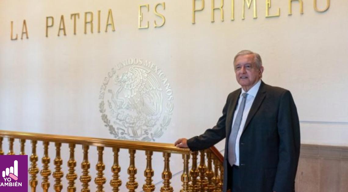 Fotografía de Andres Manuel Lopes Obrador de la cintura para arriba en palacio nacional donde al fondo se puede ver el símbolo patrio y el texto La patria es primero