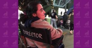 Fotografía de espaldas de Sandra Jiménez Loza. está sentada en una silla que dice director, está sonriendo y tiene el cabello detenido con una liga y viste una sudadera