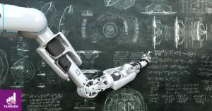Fotografía de una mano robótica escribiendo con un gis sobre un pizarrón