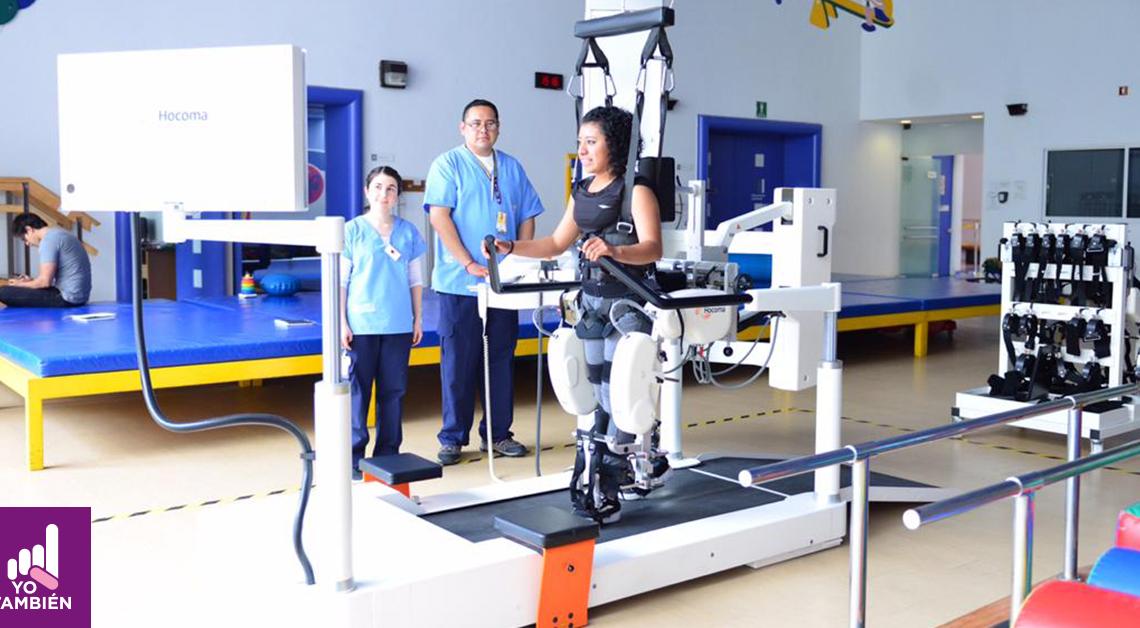 Fotografía de cuerpo completo de una mujer en un centro de rehabilitación de la fundación teletón trabajando es su rutina de ejercicios mientras 2 doctores vestidos con camisas azules y pantalones negros, la asisten