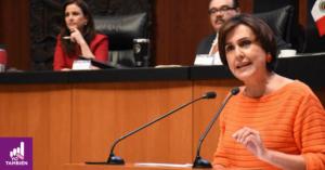 Fotografía de la senadora Patricia Mercado en la cámara de senadoras, está vestida con una blusa de color naranja. En la foto podemos ver desde sus manos para arriba y está parada frente a un estrado mientras habla al micrófono y da un discurso