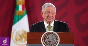 Fotografía de Andres Manuel Lopez Obrador de frente en su conferencia matutina, alncanzamos a verlo sonreir con los ojos entre cerrados. Está vestido con un traje negro y una camisa blanco. detrás de el la bandera de México.