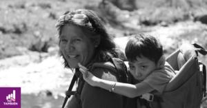 Fotografía de lado de Rosy Linares Morán y su hijo en la espalda. ambos están volteando a la cámara con una sonrisa mientras su hijo recarga su cabeza en la espalda de Rosi y con su mano hace una pequeña seña. el tiene en su brazo una pequeña pulcera de bolitas y Rosi tiene unos lentes en su cabello.