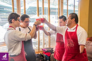 Fotografía de 4 chicos con discapacidad chocando sus bebidas en el centro felicitandose por el trabajo que hicieron ese día. Se encuentran en un starbucks y todos visten playeras blancas y unos mandiles color rojo.