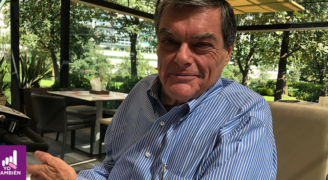 Fotografía de la cara de Federico Fleishmann viendo directo a la camara con una sonrisa, detras de el podemos ver un par de mesas de una cafeteria , árboles y arbustos. El tiene una camisa de rayas y en la bolsa tiene una pluma.