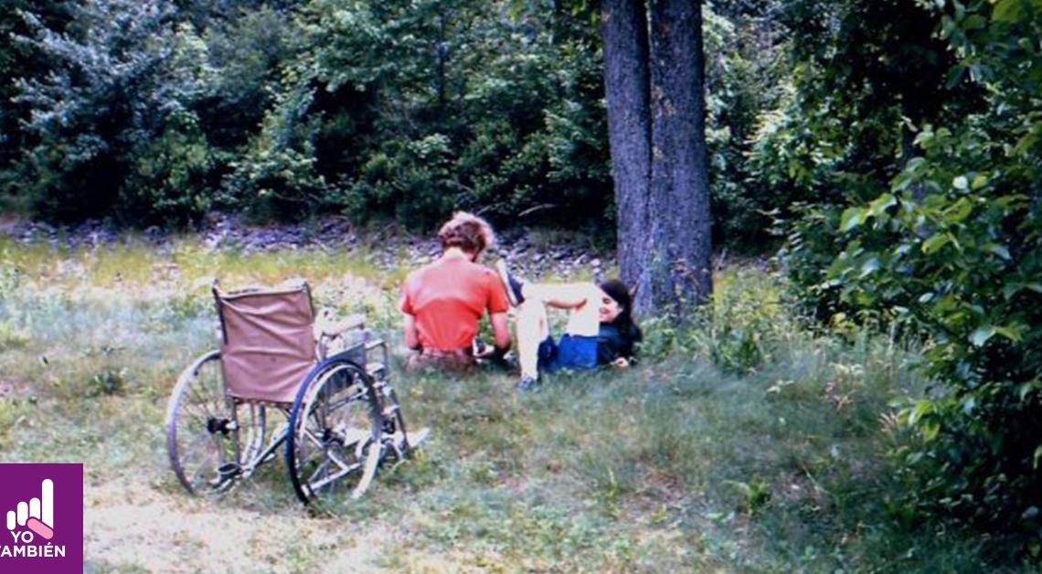 Fotografía de un par de jovenes con discapacidad sentados junto a un árbol, uno de ellos está de espaldas y el otro está junto a el recostado con su espalda en el árbol, podemos notar que están platicando.