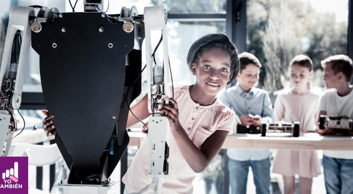 Fotografía de una niña sosteniendo el brazo de un robot mientras sonríe y ve directamente a la camara, detras de ella hay 3 niños, ellos están parados platicando al rededor de una mesa, dando a entender que es un salon de clases del futuro.