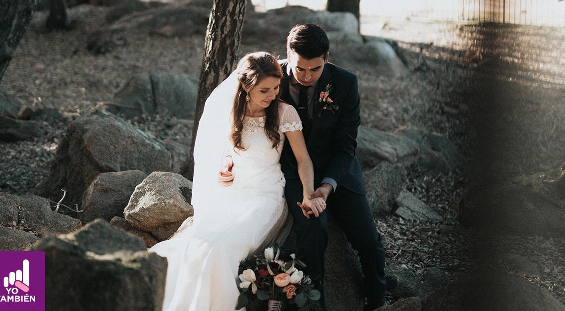 Fotografía de una pareja recién casada, están sentados en una piedra grande, ella está sentada frente a el dandole la espalda, el sentado detras está tomando su mano y los dos miran sus manos