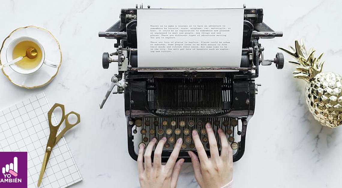 Fotografía de una maquina de escribir vista desde arriba, hay unas manos escribiendo en ella, a la izquierda hay una tasa de te y unas tijeras a la derecha una piña