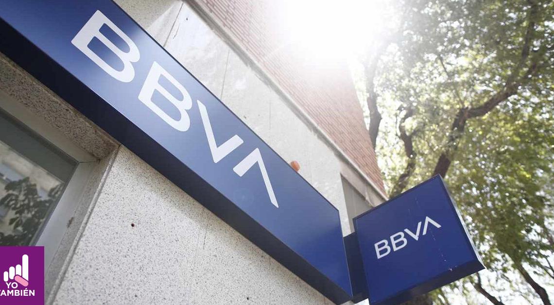 Fotografía de la entrada de uno de los bancos de Bancomer visto desde abajo, se alcanza ver un par de arboles junto al edificio donde está el banco