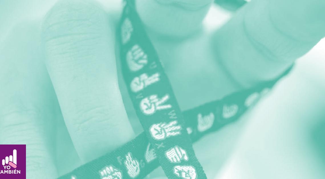 Fotografía de una mano con una pulsera de tela con dibujos de lengua de señas