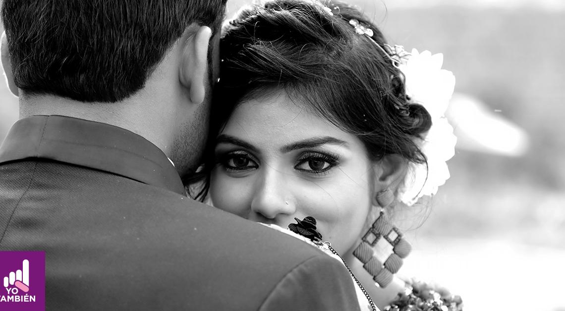 Fotografía del rostro de una mujer en su boda, ella está recargada en el pecho de su pareja y ve directamente a la camara, tiene el cabello recogido y unos aretes con forma de un cuadrado, el está de espaldas, usa un saco y tiene el cabello corto