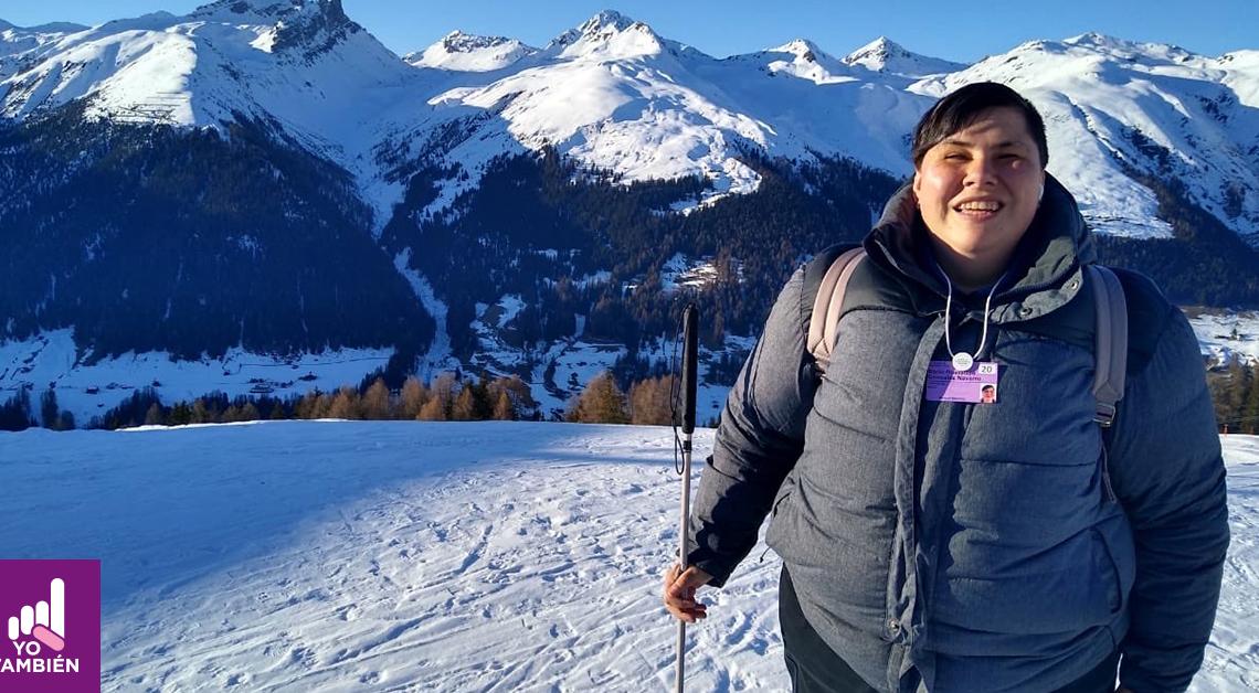 Fotografía de cuerpo completo de Rocio Gonzáles, está parada en un espacio nevado con una chamarra grande para protegerse del frio, tiene en su mano derecha un bastón y está sonriendo a la cámara, detrás de ella podemos ver montañas, todas con el pico nevado.