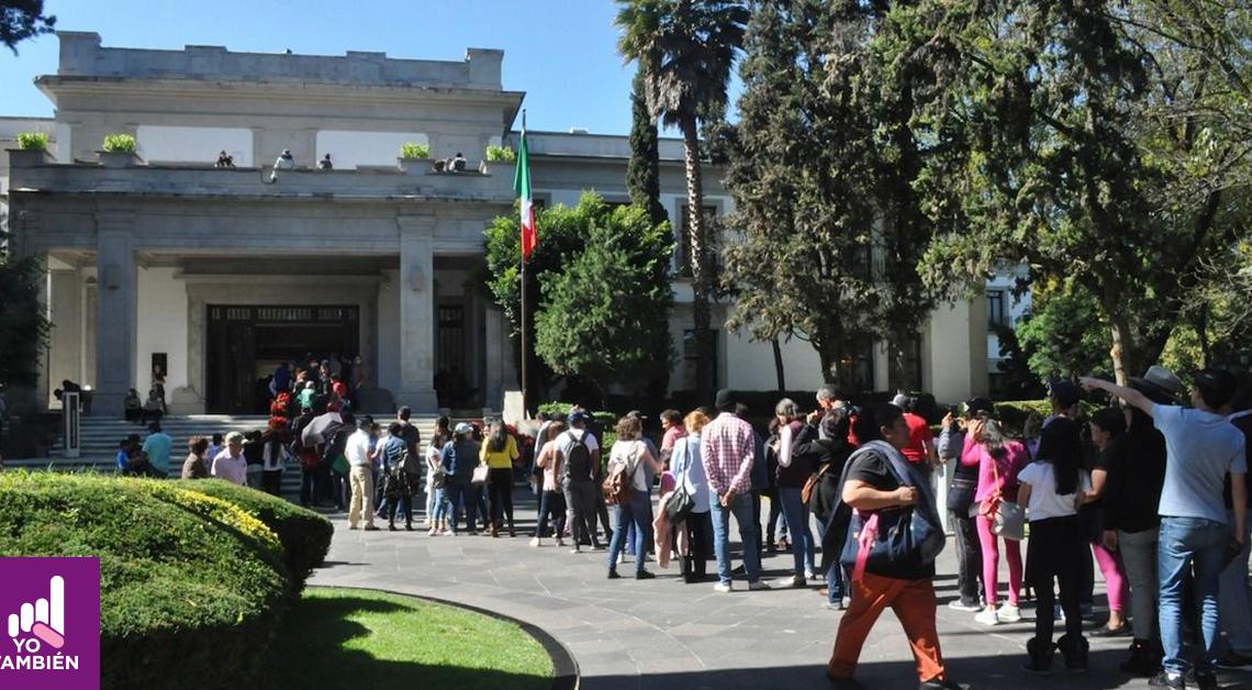 Fotografía de la entrada de Los Pinos, en la entrada hay una cola de personas esperando poder entrar a la antigua residencia presidencial, podemos notar al fondo la entrada de los pinos y junto a esta la bandera de México
