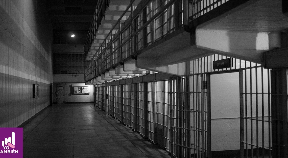 pasillo de una penitenciaria con celdas vacías y al final se ve una luz que ilumina el pasillo.