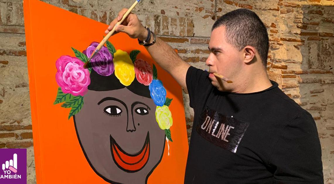 Fotografía de Alan pintando un cuadro, el está del lado derecho de la fotografía, tiene un brazo alzado con un pincel retocando las flores que tiene su pintura mientras sostiene otro pincel con la boca. El cuadro tiene el rostro de una persona con flores dibujadas a lo largo de su cabello en forma de corona