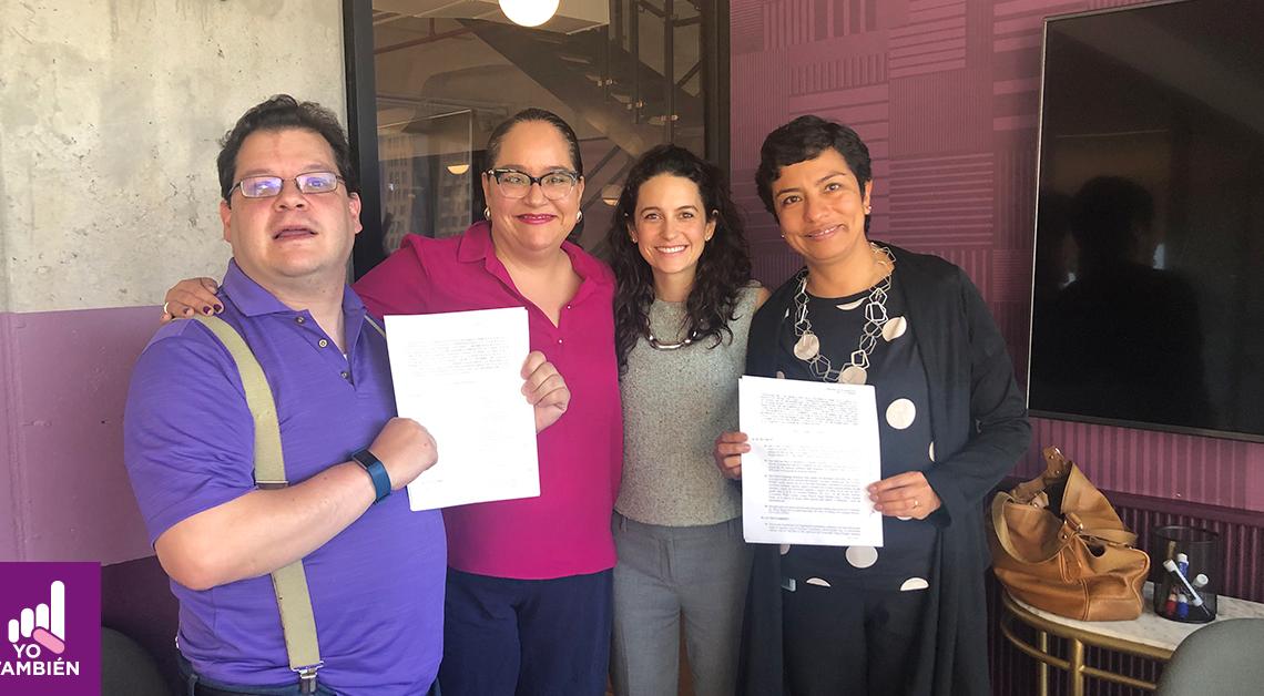 Fotografía de Katia y Agustín con 2 personas de IMCO sonriendo a la camara sosteniendo un par de hojas de papel con los acuerdos entre IMCO y Yo También