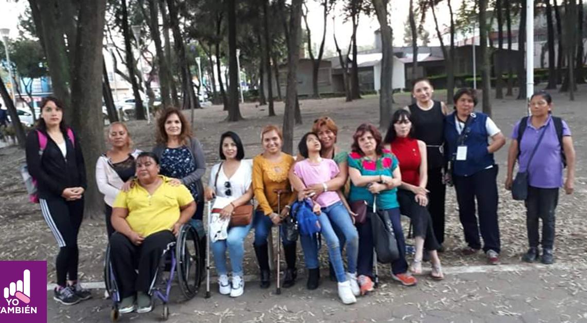 Fotografía de un grupo de 13 mujeres en un parque, todas están posando para la fotografía y tienen alguna discapacidad.