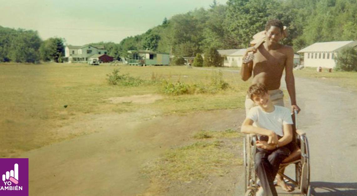 Fotografía de un hombre de color y un hombre en una silla de ruedas, el primero está sosteniendo una guitarra en su hombro mientras tiene su otra mano en la silla de ruedas mientras que el segundo sonrie a la camara con su cabeza un poco inclinada hacia la derecha, detrás de ellos se alcanza a ver un grupo de casas junto a un bosque