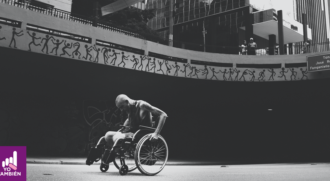 Fotografía en blanco y negro de una persona en silla de ruedas con la cabeza agachada