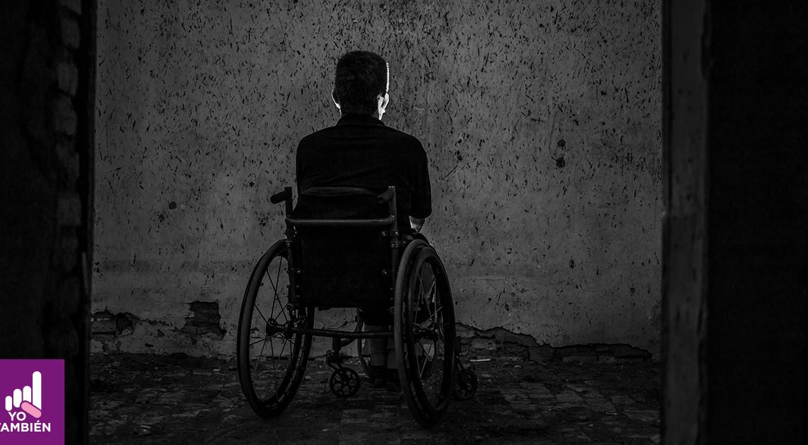 Fotografía en blanco y negro de un hombre en silla de ruedas de espaldas, está viendo directamente a una pared sin nada pasando una puerta
