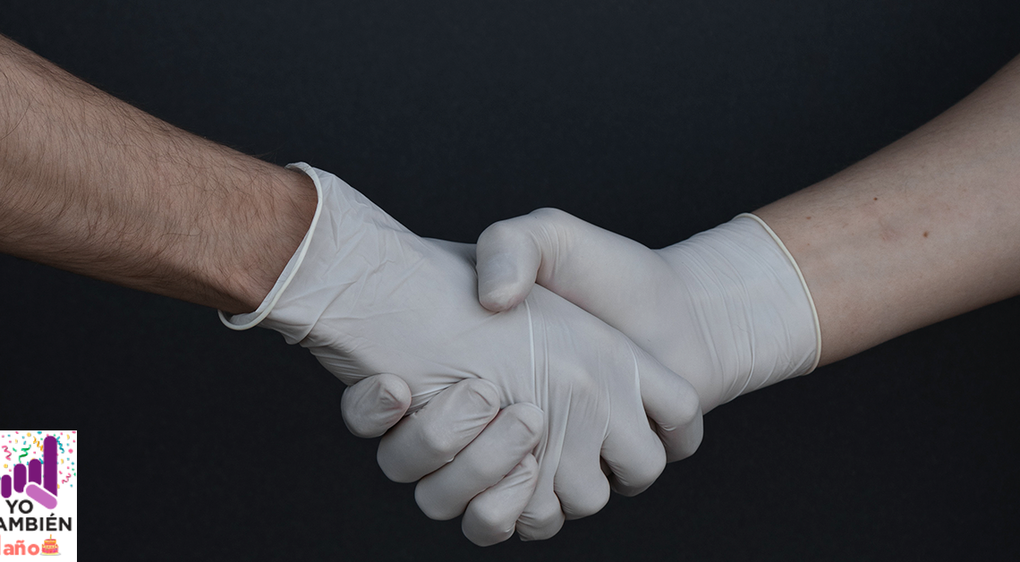 Fotografía de un par de manos saludandose con guantes puestos