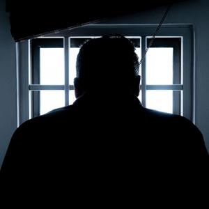 Fotografía de la silueta de un hombre, frente a el se alcanza a ver una ventana con barrotes