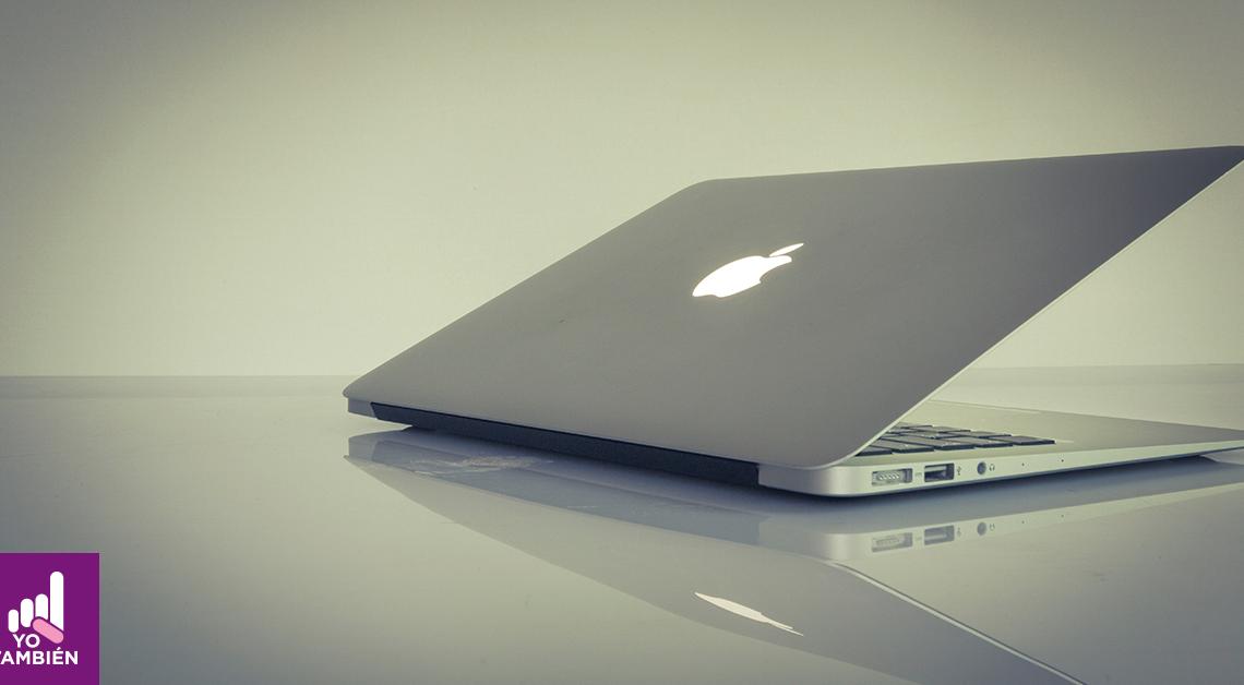Fotografía de una laptop entre abierta sobre una mesa, en ella se alcanza a ver su reflejo