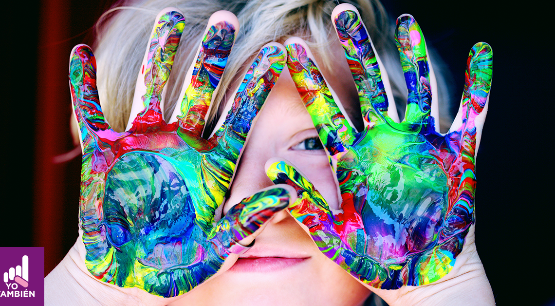 Fotografía del rostro de un niño cubierto por sus manos. estas tienen pintura y detras de ellas alcanzamos a ver su ojo izquierdo y su boca
