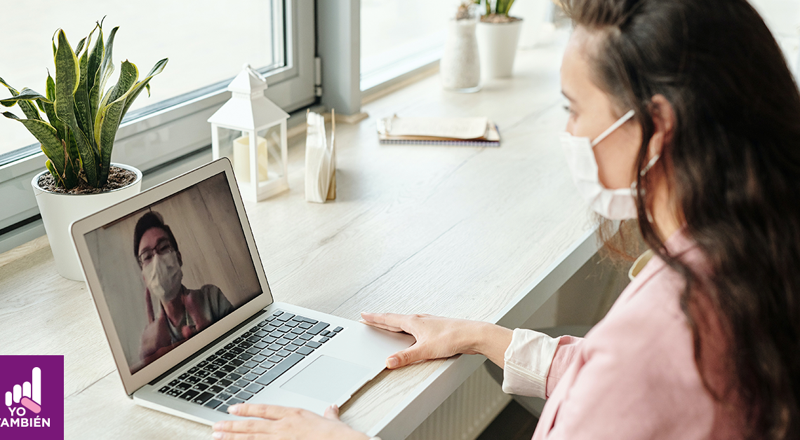 Fotografía de una mujer frente a una computadora tomando clase, ella esta usando un cubrebocas y tiene sus manos sobre la computadora. En ella se alcanza a ver otra persona con cubrebocas