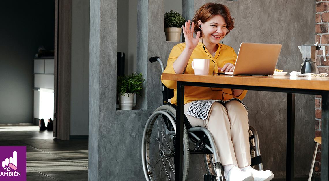 fotografía de una mujer sentada en su silla de ruedas, frente a ella una mesa con una computadora. ella hace una señal de saludo hacia la computadora