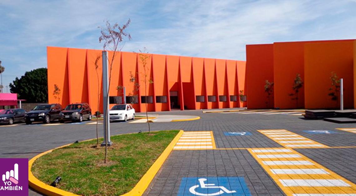 Fotografía del estacionamiento de las instalaciones del teletón donde se alcanza a ver a lo lejos la entrada y un par de carros estacionados
